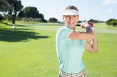 stock photo of ladies golf  - Lady golfer teeing off and smiling at camera on a sunny day at the golf course - JPG