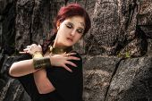 picture of tunic  - Beautiful makeup girl wearing black tunic and an antique jewels rocky wall on background - JPG