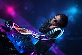 pic of disc jockey  - Young disc jockey playing music with electro light effects and lights - JPG