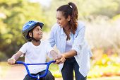 picture of mother-in-love  - loving mother help her cute son ride a bicycle - JPG