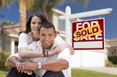 stock photo of yard sale  - Young Happy Hispanic Young Couple in Front of Their New Home and Sold For Sale Real Estate Sign - JPG