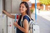 stock photo of hispanic  - Cute Hispanic girl carrying some books and a backpack in high school - JPG