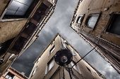 stock photo of pov  - point of view of a dark alley with gloomy sky in Venice Italy - JPG