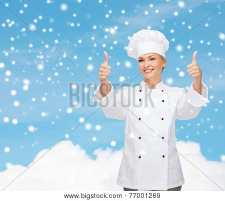 christmas, cooking, profession, gesture and people concept - smiling female chef showing thumps up over blue snowy sky and cloud background