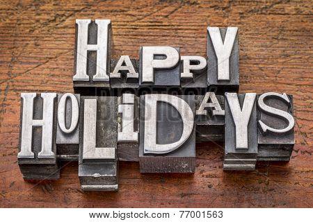 Happy Holidays greetings  in vintage metal type printing blocks over grunge wood