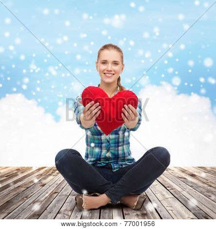 love, charity, holidays and people concept - young woman with red heart pillow sitting on wooden floor over blue snowy sky and cloud background