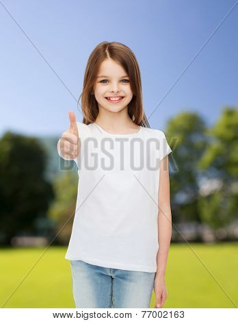 advertising, childhood, nature and people - smiling little girl in white blank t-shirt showing thumbs up gesture over green park background