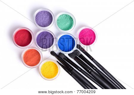 Set of bright matte mineral eye shadows and brushes, top view isolated on white background
