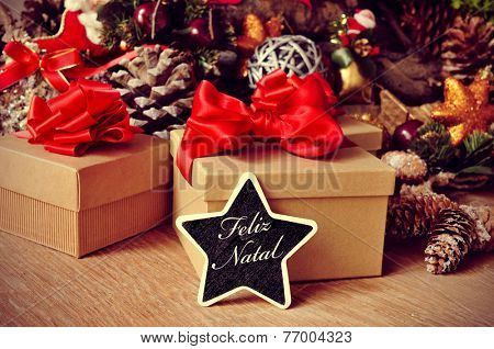 a star-shaped chalkboard with the text feliz natal, merry christmas in portuguese, on a rustic wooden table full of gifts and christmas ornaments, such christmas stars and pine cones