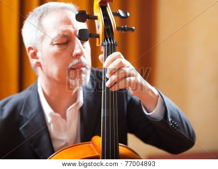 Portrait of a man playing a cello in a concert hall