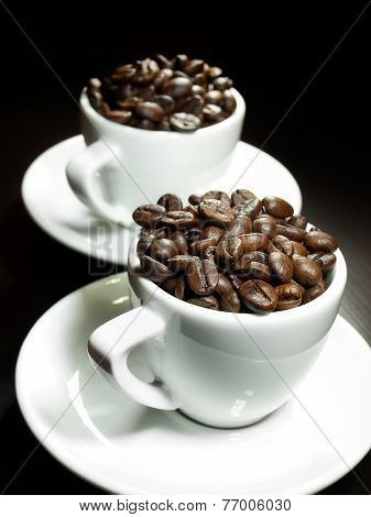 Two coffee cups full of coffee beans