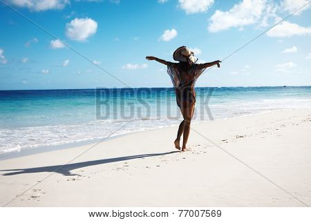 Beautiful  woman in hat on tropical beach