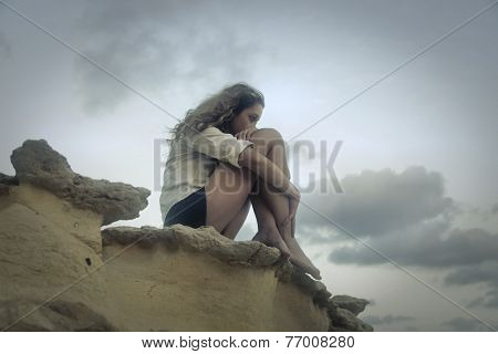 Lonely girl sitting on a rock