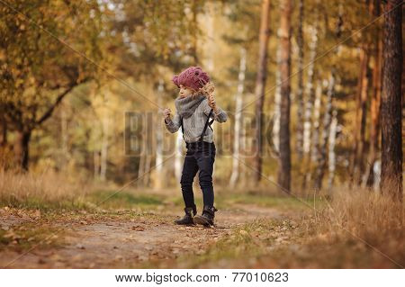 Cute child girl playing in autumn forest