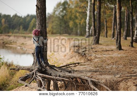Child girl climbing old pine at autumn riverside