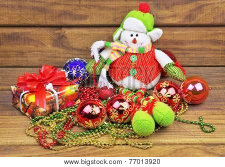 Christmas Toy Balls With Snowman, Gifts, Beads, On Wooden Background. Christmas Decoration.