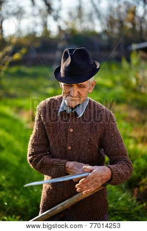 Old Farmer Sharpening Scythe