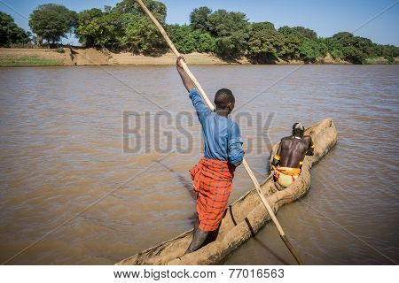 Men Cross The Omo River Near Turmi Using A Wooden Boat, Ethiopia.