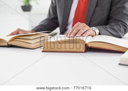 Businessman sitting at desk reading books in his office