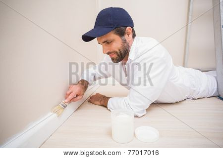 Painter painting the skirting boards in a new house