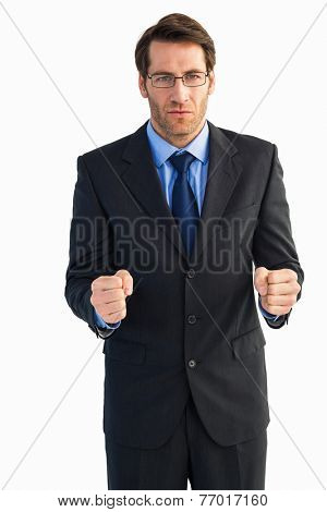 Angry businessman with closed fists looking at camera on white background