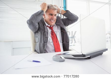 Stressed businessman at his desk in his office
