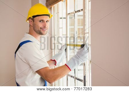 Construction worker using measuring tape in a new house