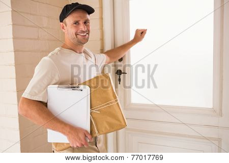 Smiling handyman knocking at the door of someones home