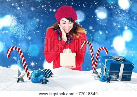Surprised brunette holding a gift against christmas scene with gifts and candy canes
