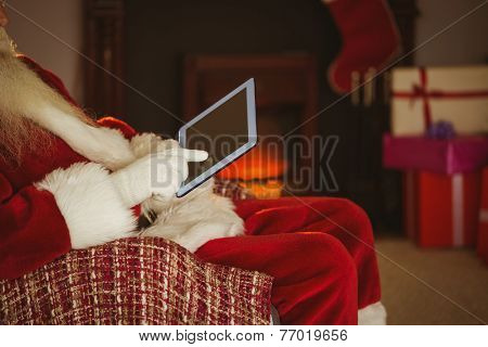 Mid section of santa touching tablet at home in the living room