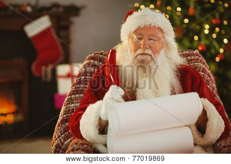 Santa claus writing his list with a quill at home in the living room