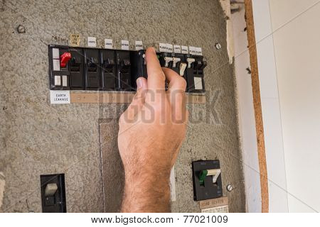 Electrician working on the fuse box in the kitchen