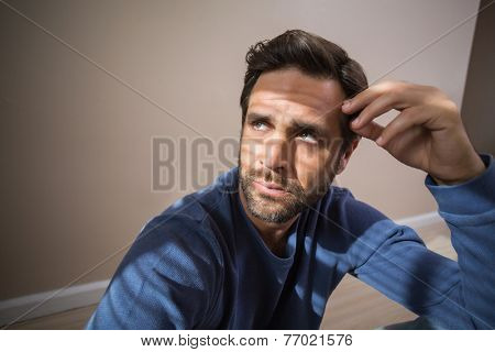 Depressed man sitting on floor in an empty room