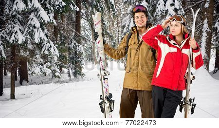 Two skiers holding their skies in the deep powder snow in a forest during their winter holiday
