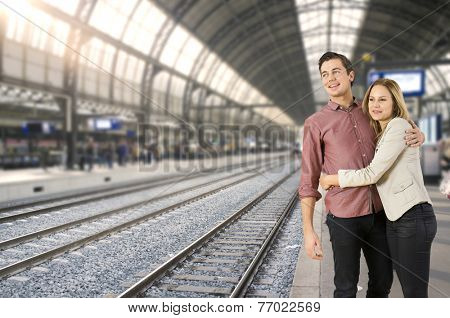Young couple hugging each other on a train station, waiting for a train to arrive, ready to go places.