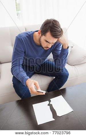 Confused man looking at torn page at home in the living room