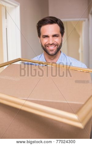 Happy man carrying moving box and frame in his new home