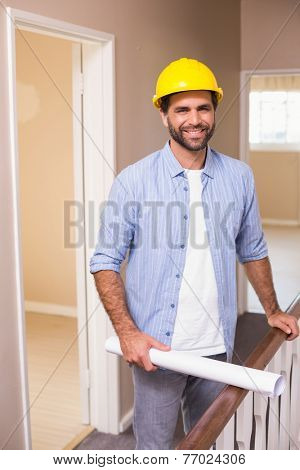 Casual architect smiling at camera in a new house