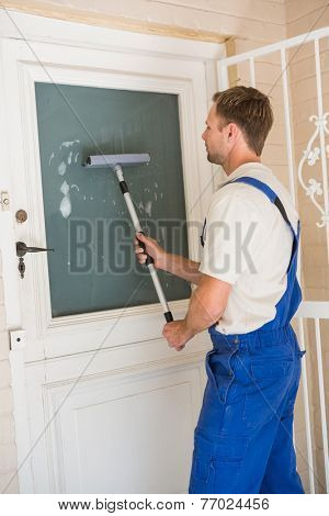Handyman cleaning the window with squeegees in a new house