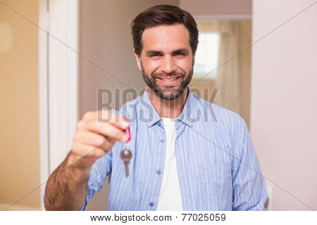 Casual man showing his house key in his new home