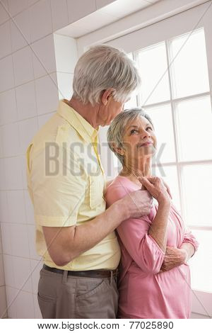 Senior couple looking out their window at home in the kitchen