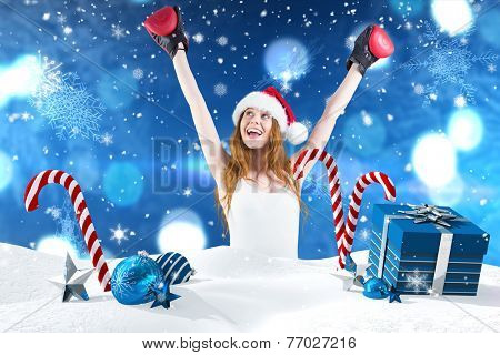 Festive redhead cheeering with boxing gloves against christmas scene with gifts and candy canes