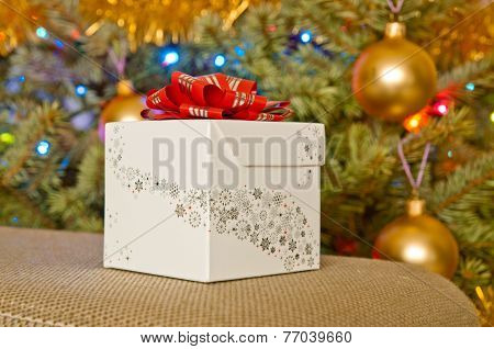White Christmas Gift Next To A Christmas Tree