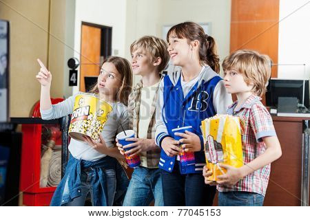 Cute girl showing something to siblings with snacks at cinema