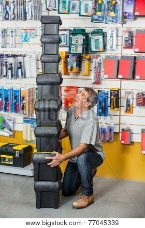 Full length of mature man shouting while carrying stacked toolboxes in hardware store