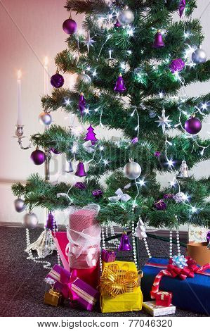 Decorated Christmas Tree With Gifts Around And With The Lit Candlestick