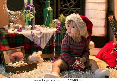 Baby In Santa Hat Sitting On The Carpet With A Cap