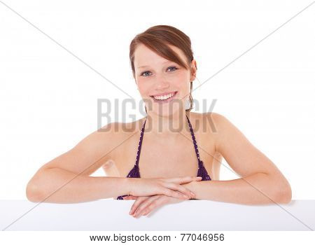 Attractive young woman in bikini behind white placeholder. All on white background.