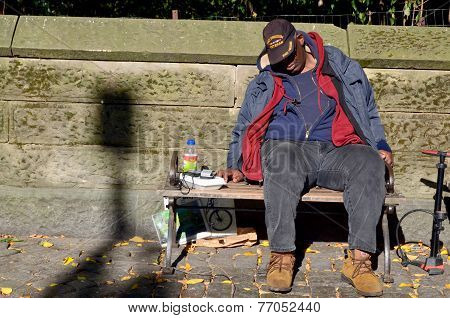 A homeless man sleeping on bench park