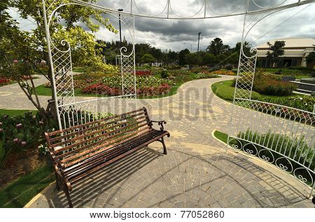 Bench In A Garden With Flowers And Arbor - Nice And Neeat Outdoor Park